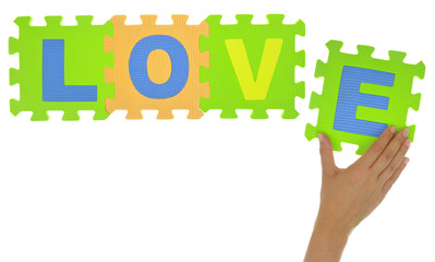 "Hand forming word ""Love"" with jigsaw puzzle pieces isolated"