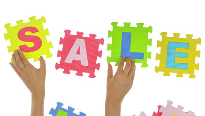 "Hands forming word ""Sale"" with jigsaw puzzle pieces isolated"