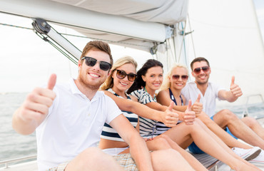 smiling friends on yacht showing thumbs up