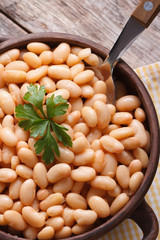 boiled white beans in a bowl on wooden macro vertical top view