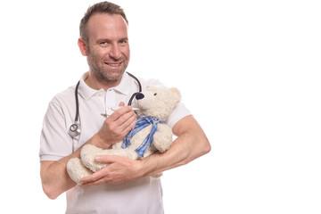 Lächelnder Kinderarzt mit einem Teddybären misst Fieber