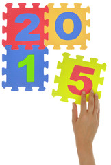 "Hand forming ""2015"" with jigsaw puzzle pieces isolated"