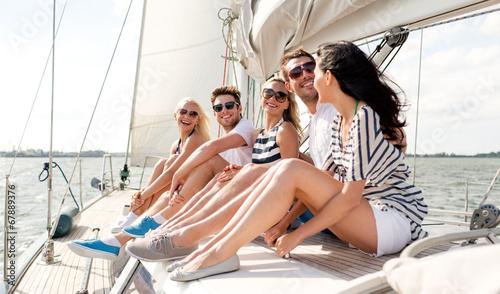 Leinwanddruck Bild smiling friends sitting on yacht deck
