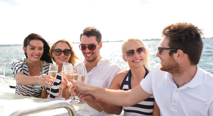smiling friends with glasses of champagne on yacht