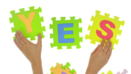 "Hands forming word ""Yes"" with jigsaw puzzle pieces"