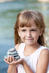 Little girl holding pyramid of stones