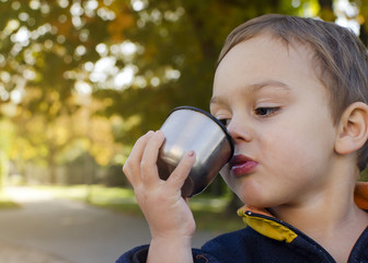 Child drinking tea in park
