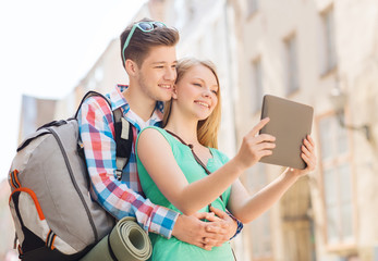 smiling couple with tablet pc and backpack in city