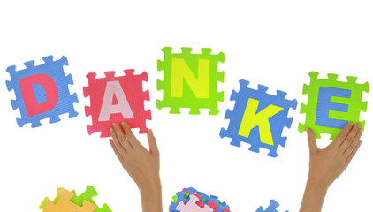 "Hands forming word ""Danke"" with jigsaw puzzle pieces isolated"
