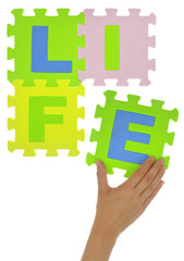 "Hand forming word ""Life"" with jigsaw puzzle pieces isolated"