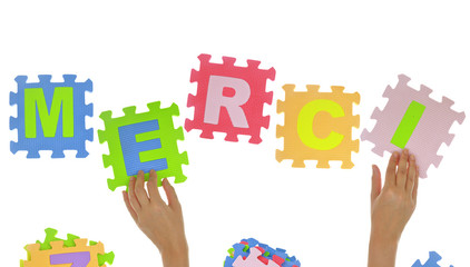 "Hands forming word ""Merci"" with jigsaw puzzle pieces isolated"