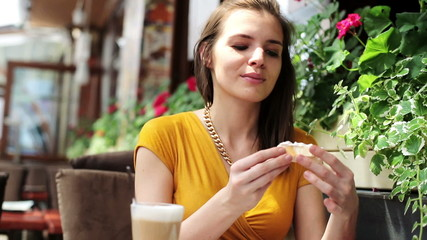 Woman spreading paste on slice of bread in restaurant