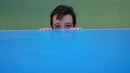 Niño asomándose tímidamente