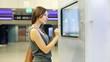 Woman checking trains timetable at modern touchscreen info kiosk