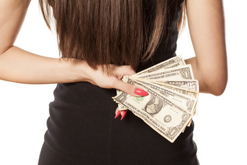 A woman holds a bunch of money behind her back