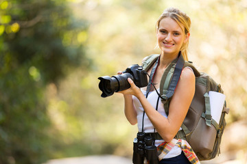 young woman holding a dslr camera in mountain