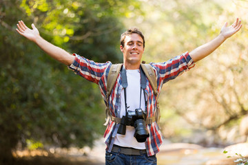 young photographer arms open in mountain