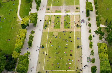 Crowd of tourists relaxing in Champs de Mars gardens, under the