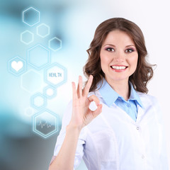 Young beautiful doctor on bright blue background