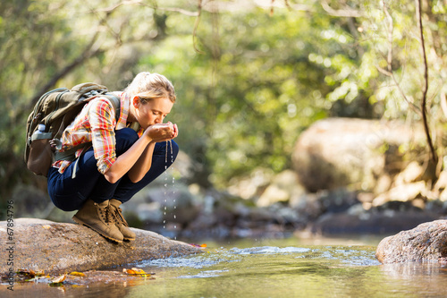 young hiker drinking stream water - 67894796