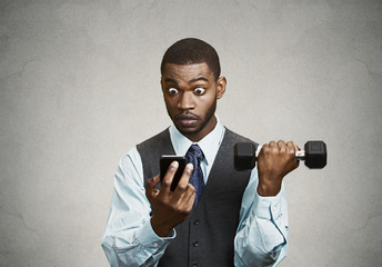 Corporate executive shocked news on smart phone lifting weight