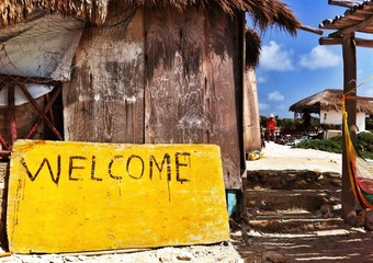 yellow painted wellcome sign on the beach in Mexico