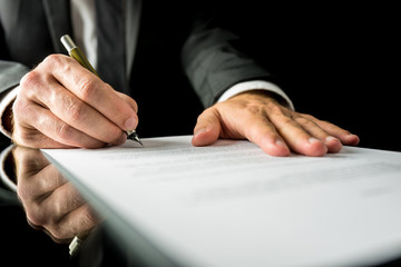 Businessman signing a paper document