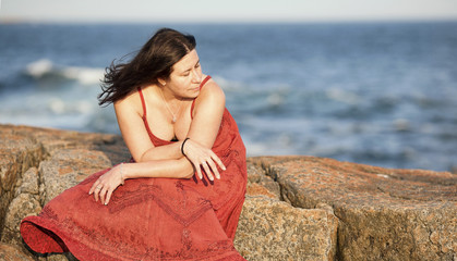 Woman in red on rocky beach at sunset 4