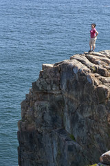 Young woman at the top of a cliff overlooking the ocean