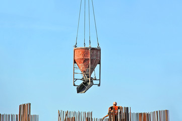 Crane lifting concrete mixer container against blue sky