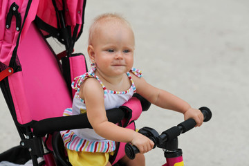 Cute baby girl riding her first bicycle