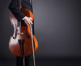 Cello musician standing with a dark background.