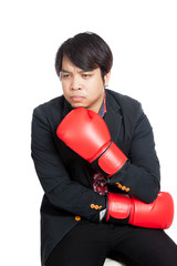 Asian man wear boxing gloves thinking of something