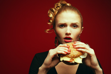 Fashion & Gluttony Concept. Rred-haired model eating burger