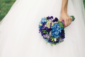 Bride's hand with wedding bouquet over white dress