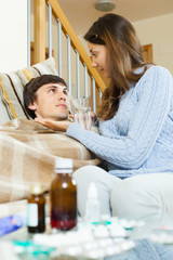 Girl giving  medicament to unwell husband