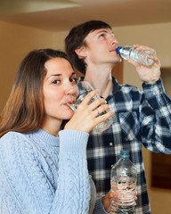 Young couple in their home drinking water