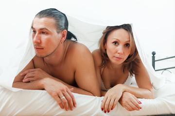 Unhappy couple under sheet