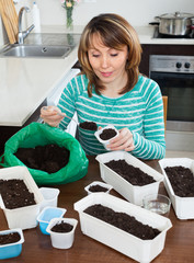 Ordinary girl in green making soil for seedlings