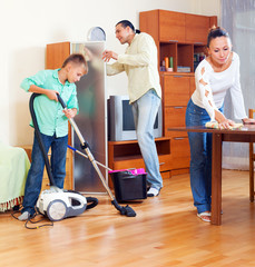 Parents and  boy cleaning  in  room