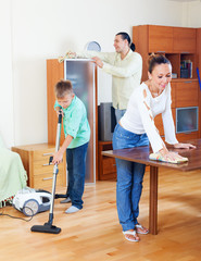 Happy family of three   cleaning in home