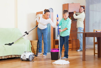 Happy family vacuuming at home