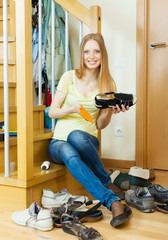 Happy long-haired woman cleaning shoes