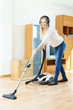 Woman in headphones cleaning with vacuum cleaner