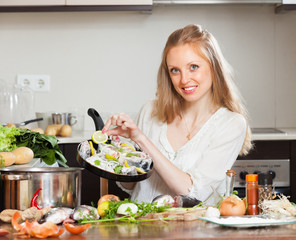 girl cooking fish with lemon  at home