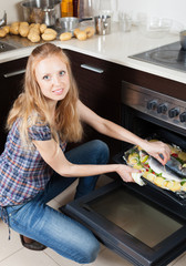 Ordinary woman cooking raw fish in oven