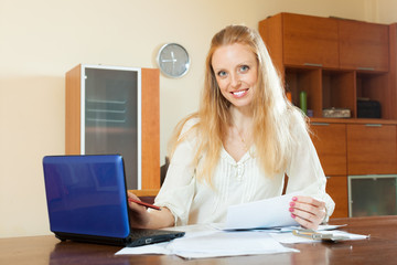 pensive blonde woman working with financial documents