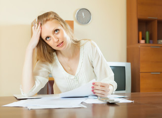 Sad woman with financial documents at home