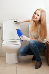 Happy woman cleaning toilet bowl with sponge
