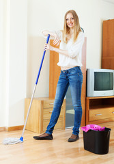 Positive long-haired girl washing parquet